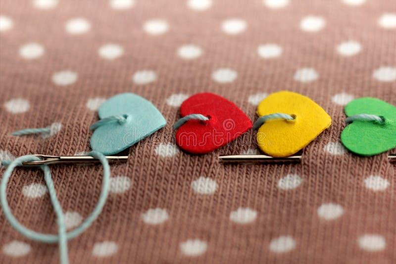 makroen av färgrika hjärtor sydde på prickigt tyg med visaren och tråden arkivbilder