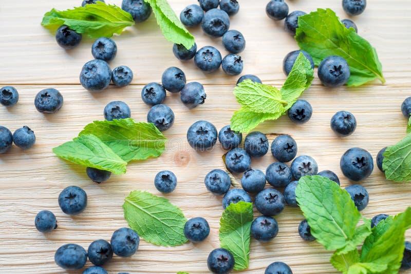 Makrofoto av blåbär på en trätabell Bästa sikt på mintkaramellsidor med björnbär sund frukost royaltyfri fotografi