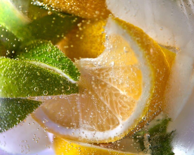 Makrofoto av nya limefrukt- och citronskivor med bubblor i exponeringsglaset Kall drink f?r sommar royaltyfri fotografi