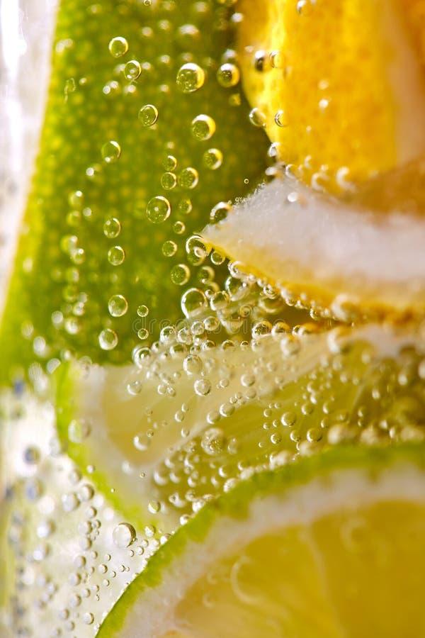 Makrofoto av nytt gjord lemonad med stycken av limefrukt, citron och bubblor i ett exponeringsglas Uppfriskande drink f?r sommar arkivfoto