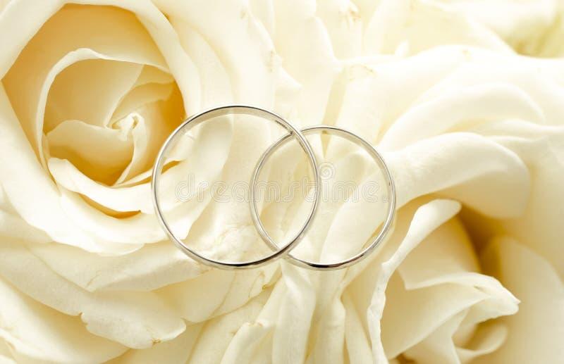 Makrofoto von zwei Eheringen, die auf Brautblumenstrauß liegen stockfoto