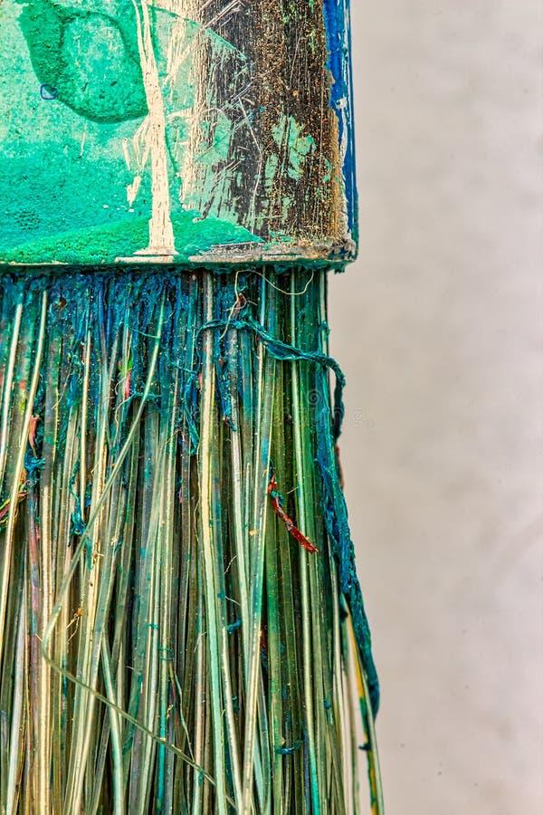 Makrofotografi av en använd borste - detalj av metallringen och borsten av en använd borste med kvarlevor av torr målarfärg royaltyfri fotografi