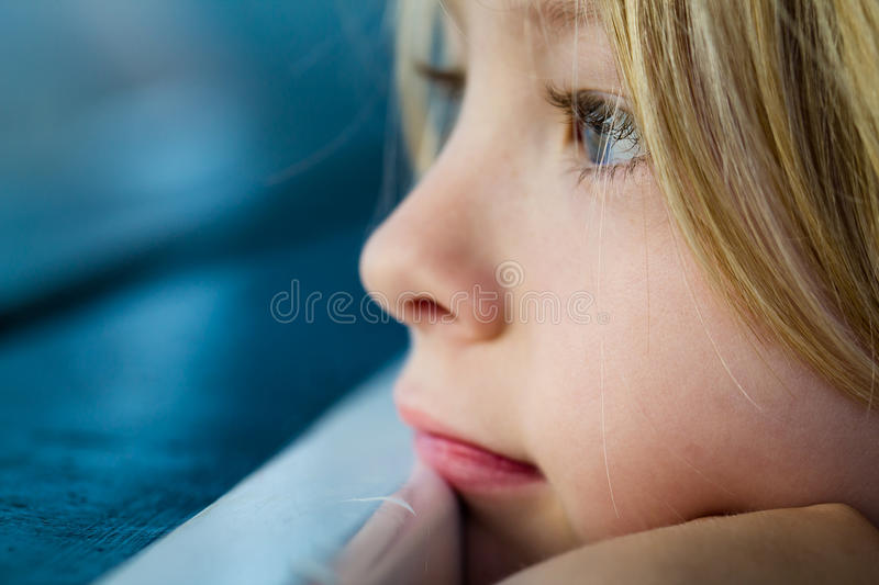 Makronärbild av det ledsna barnet som ser ut ur fönster fotografering för bildbyråer