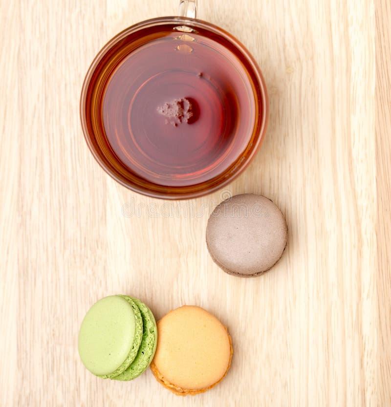Makron och glass kopp av svart te ovanför blå tonad hjälpmedelsikt arkivfoton
