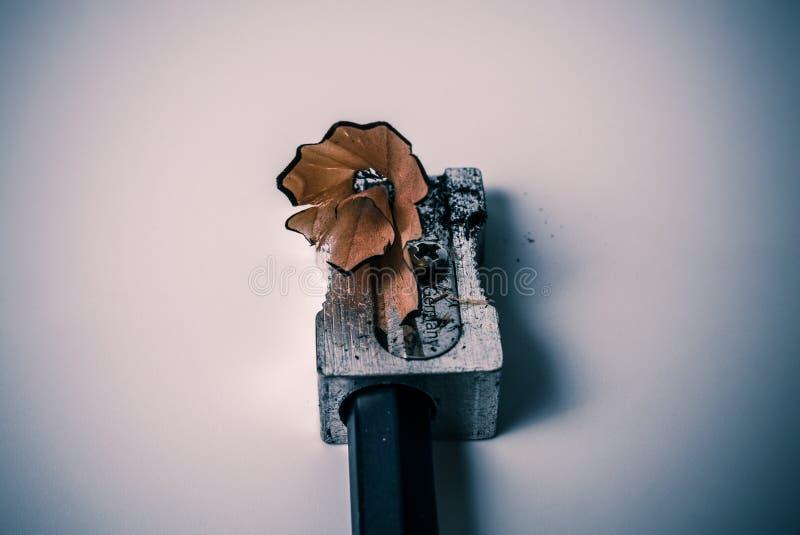 Makronahaufnahme des Schärfens eines Bleistifts mit einem grauen Metallbleistiftspitzer mit dem hölzernen rasierenden Strudel - K lizenzfreie stockbilder