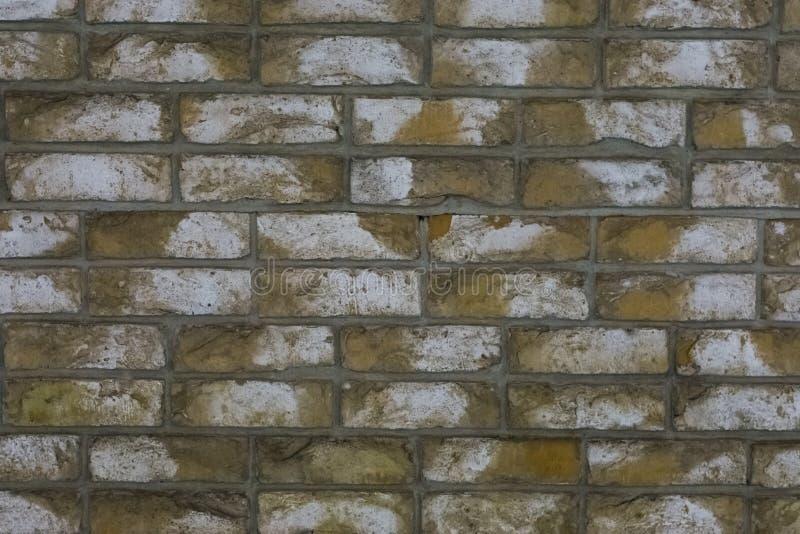 Makronahaufnahme einer gelben Steinbacksteinmauer mit weißen Flecken, ein Architekturhintergrund stockfoto