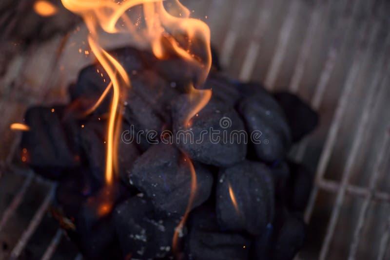 Makronahaufnahme von Flammen auf Holzkohlen in der Grillgrube stockfotografie