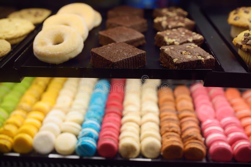 Makrone, Schaumgummiringe, Kekse, Muffins im Fenster eines Cafés oder Speicher stockbilder
