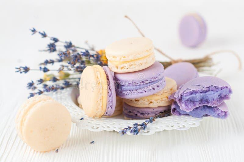 Makronen mit und Blumenstrauß von Lavendelblumen lizenzfreie stockbilder