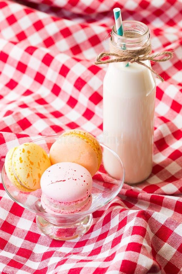 Makronen und Milch in einer Flasche mit gestreiften Strohen stockfoto