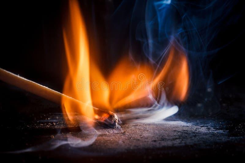 Makroschießen eines brennenden Matches mit einer Flamme des Feuers stockbilder