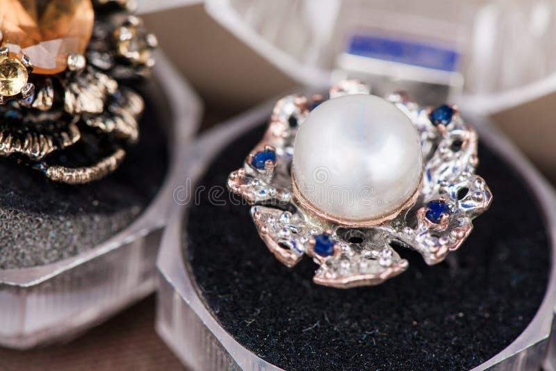 Makroschuß des silbernen Verlobungsrings in der Geschenkbox auf buntem, funkelndem Hintergrund stockfotos