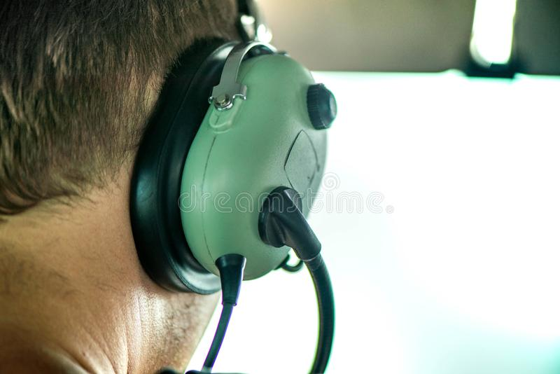 Makroskott av den pilot- bärande flyghörlurar med mikrofon och flyga med den lilla nivån och samtal med dispatcheren royaltyfria bilder
