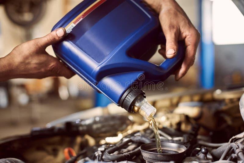 Makrovy av blå flaska i smutsiga händer som häller olja i bilmotor Ersätta motorsmörjmedel i centret för automatisk service arkivbilder