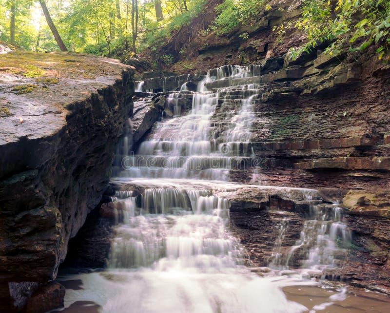 Makt av en vattenfall matchas av makten av en stenblock fotografering för bildbyråer