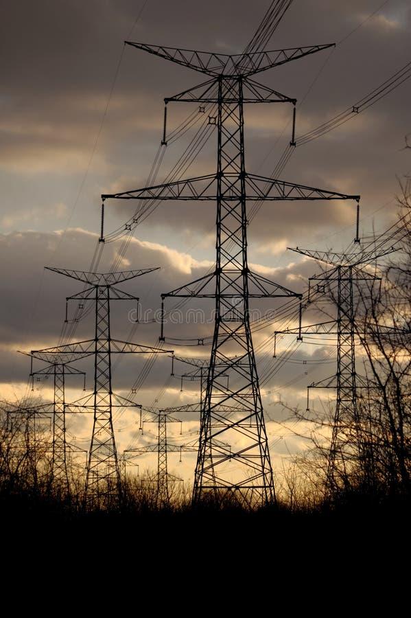 Makt - elektricitetspyloner och linjer på solnedgången royaltyfri fotografi