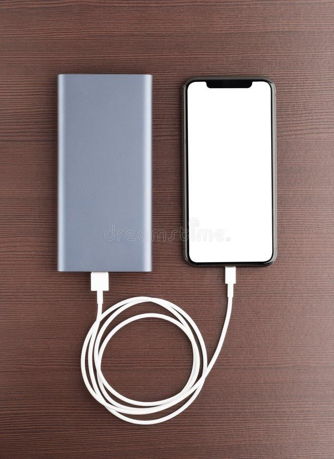 Maktbank och smartphone på trätabellen royaltyfri fotografi