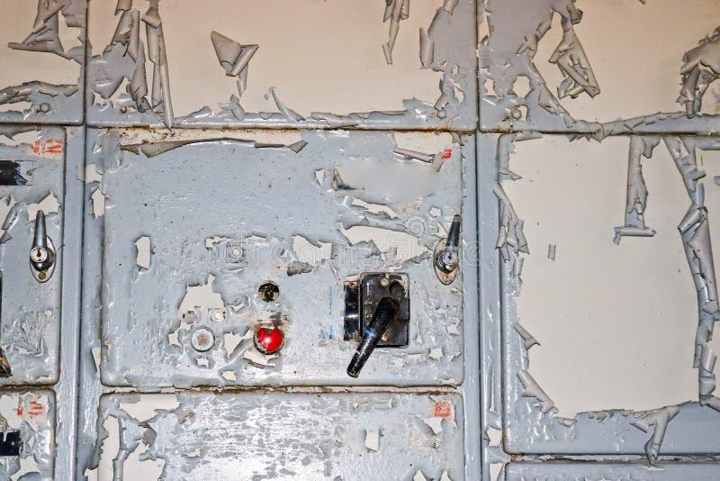 Maktknappen och knoppvippströmbrytaren som kontrollerar industriell utrustning på fabriken på bakgrunden av en vägg med sjaskigt arkivfoton