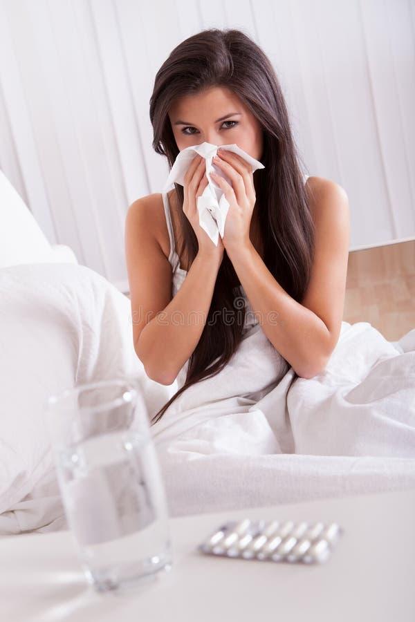 Mal da mulher na cama com um frio e uma gripe imagem de stock