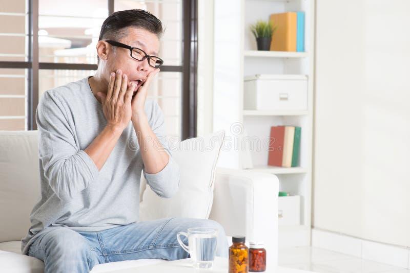 Mal de dents asiatique mûr d'homme images stock