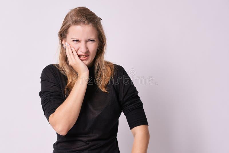 Mal de dents Sensations désagréables Jeune fille Fond blanc photo stock