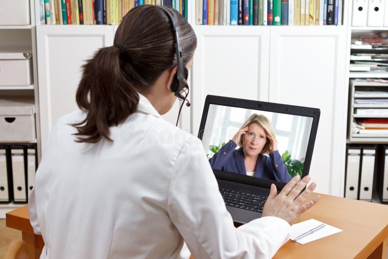 Mal de tête de patient d'ordinateur portable de casque de docteur image libre de droits