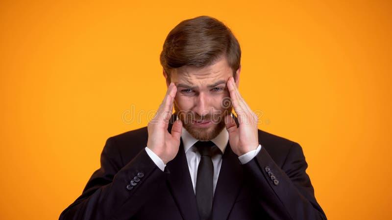 Mal de t?te fort ?puis? de sentiment d'homme d'affaires, massant des temples, le travail stressant image stock