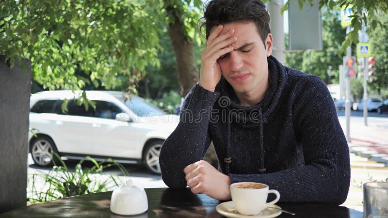 Mal de tête, jeune homme tendu dans la terrasse de café photos stock