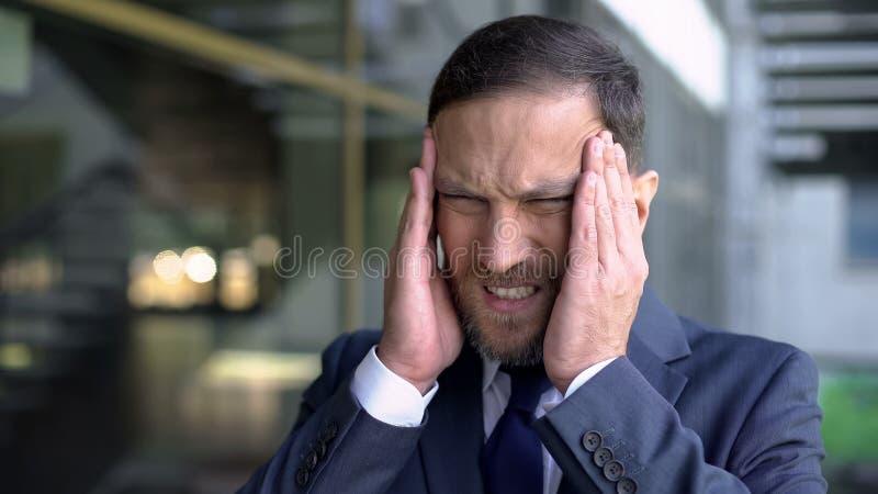 Mal de tête masculin soumis à une contrainte de sentiment des employés, massant des temples, bruit de ville, crise image libre de droits