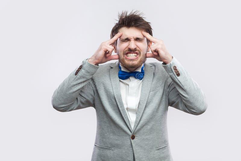 Mal de tête Portrait de malade ou inquiéter l'homme barbu le costume gris occasionnel et la position bleue de noeud papillon et e photographie stock