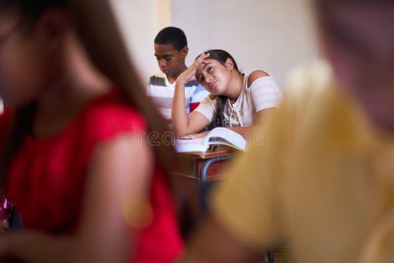 Mal de tête pour l'étudiant soumis à une contrainte par malade Girl In Class à l'école image stock