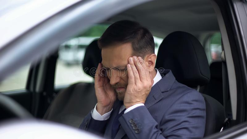 Mal de tête soumis à une contrainte de sentiment d'homme d'affaires dans la voiture, massant des temples, tension artérielle photos libres de droits