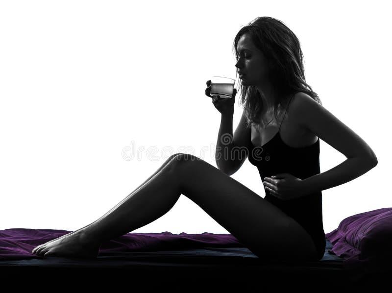 Mal de ventre de nausée de femme stitting en silhouette de lit images stock