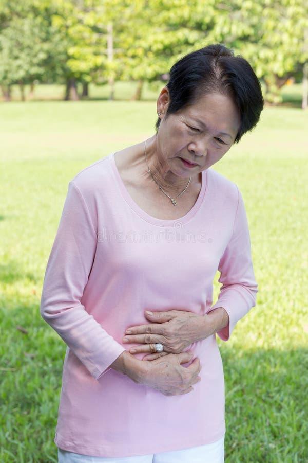 Mal de ventre supérieur asiatique de femmes images libres de droits