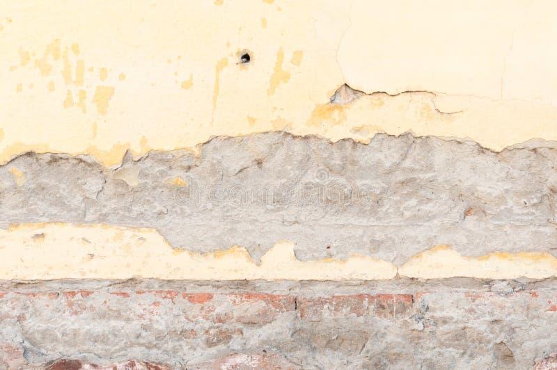 Mala base de la fundación en casa vieja o pared agrietada constructiva de la fachada del yeso con el fondo del ladrillo imagen de archivo