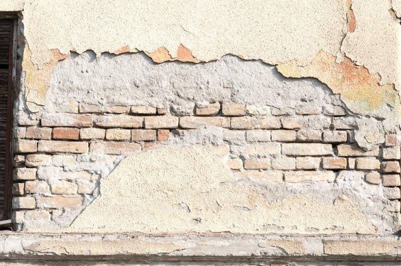 Mala base de la fundación en casa vieja o pared agrietada constructiva de la fachada del yeso con el fondo del ladrillo fotos de archivo