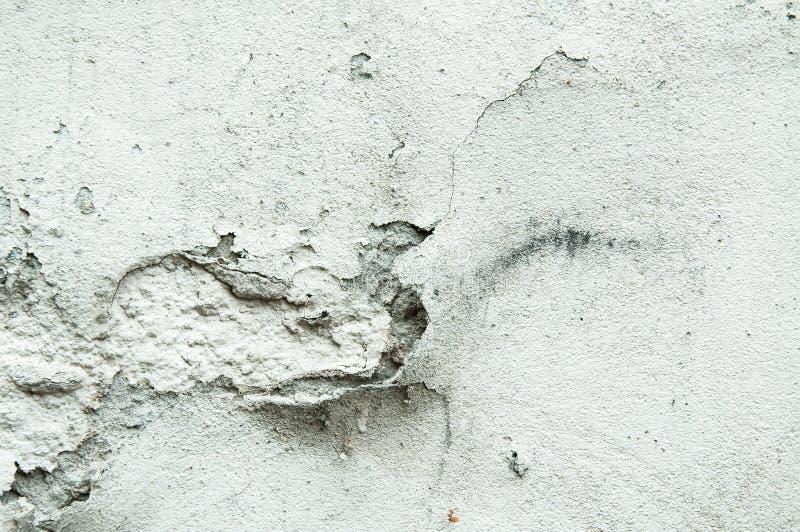 Mala base de la fundación en casa vieja o pared agrietada constructiva de la fachada del yeso con el fondo del ladrillo foto de archivo