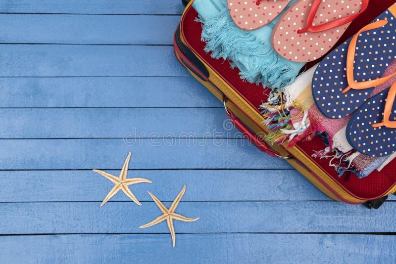 Mala com flip-flops e toalhas de praia em mesa de madeira fotografia de stock
