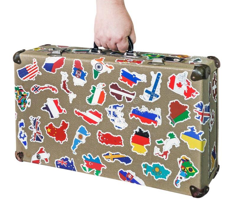 Mala de viagem à disposição com etiquetas das bandeiras dos países do curso imagens de stock