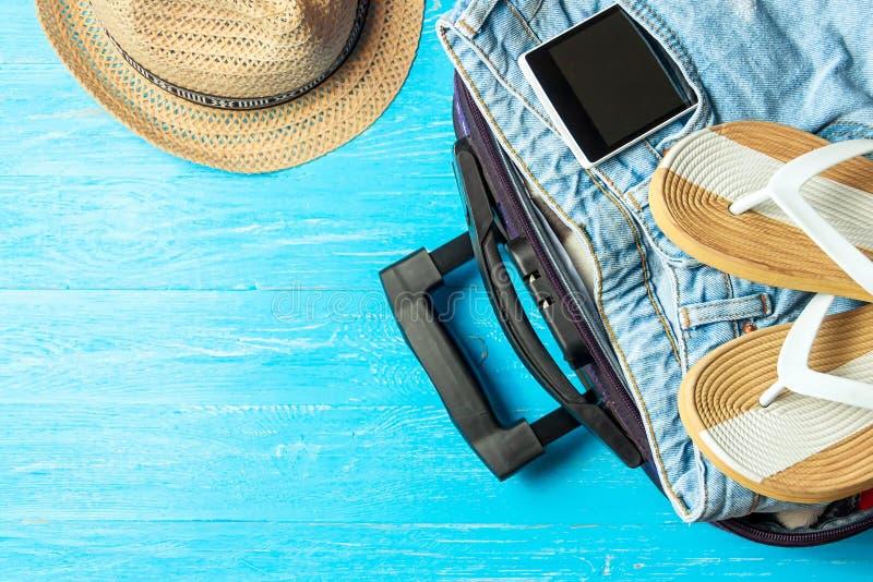 Mala de viagem aberta com os acessórios do curso na tabela de madeira azul com copyspace foto de stock royalty free