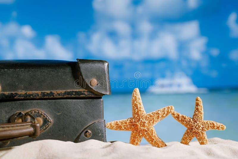 Mala de viagem antiga retro velha na praia com estrela do mar, mar e céu b fotografia de stock royalty free