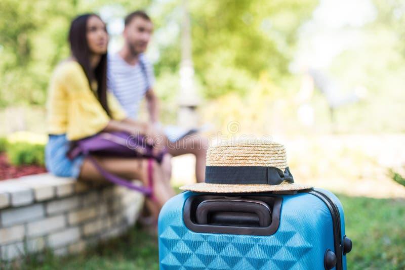 Mala de viagem com chapéu de palha e pares de viajantes que sentam-se atrás fotografia de stock royalty free