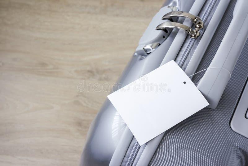 Mala de viagem com etiqueta vazia da etiqueta no assoalho de madeira imagem de stock royalty free