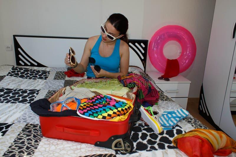 Mala de viagem da embalagem da moça na cama em casa foto de stock royalty free