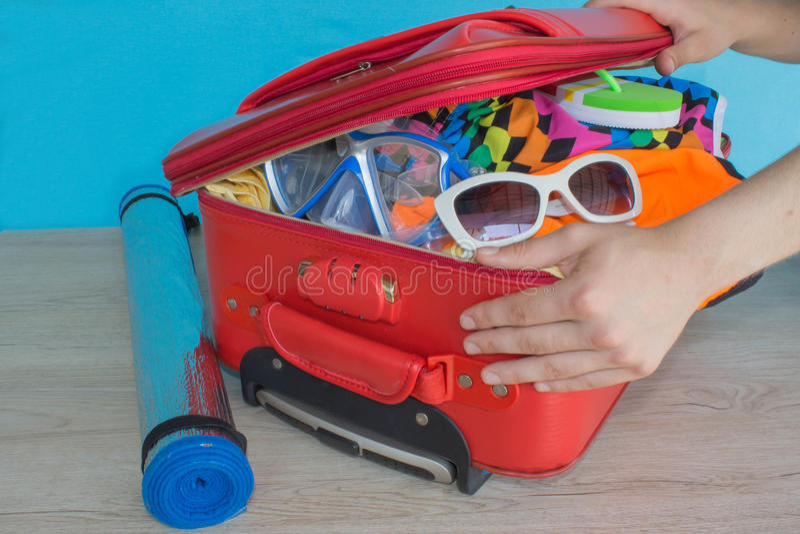 Mala de viagem da embalagem da mulher Material da embalagem da mulher na mala de viagem em casa Conceito do curso e das férias imagem de stock