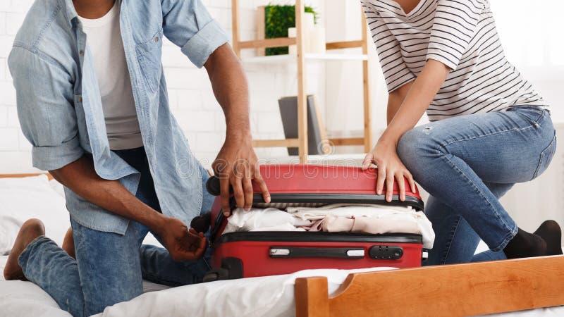 Mala de viagem da embalagem Pares que tentam fechar o valise fotos de stock