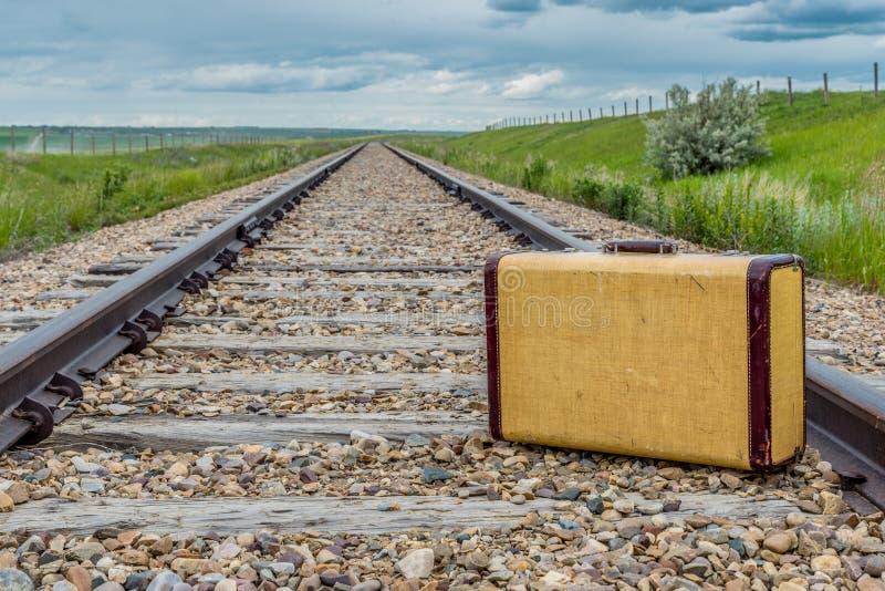 Mala de viagem do vintage no meio de trilhas de estrada de ferro nas pradarias fotografia de stock