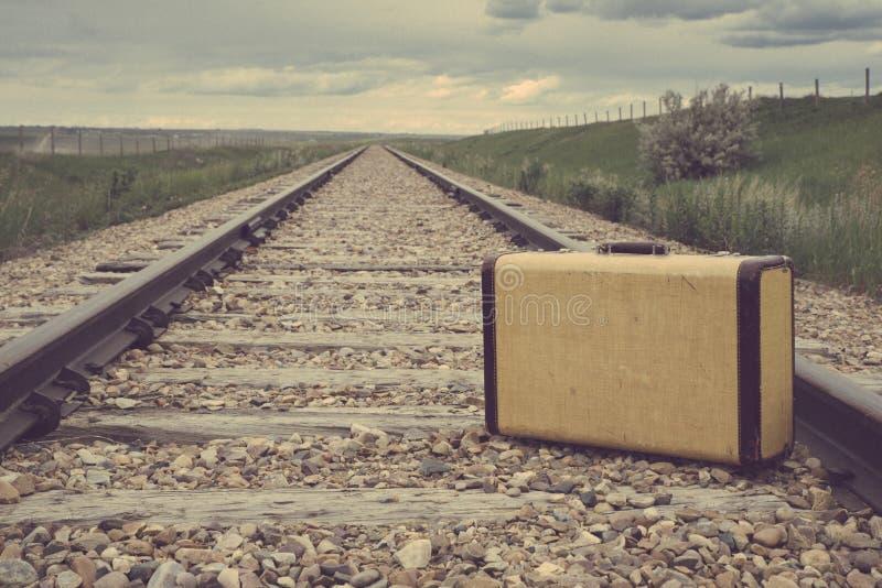 Mala de viagem do vintage no meio de trilhas de estrada de ferro nas pradarias fotos de stock royalty free
