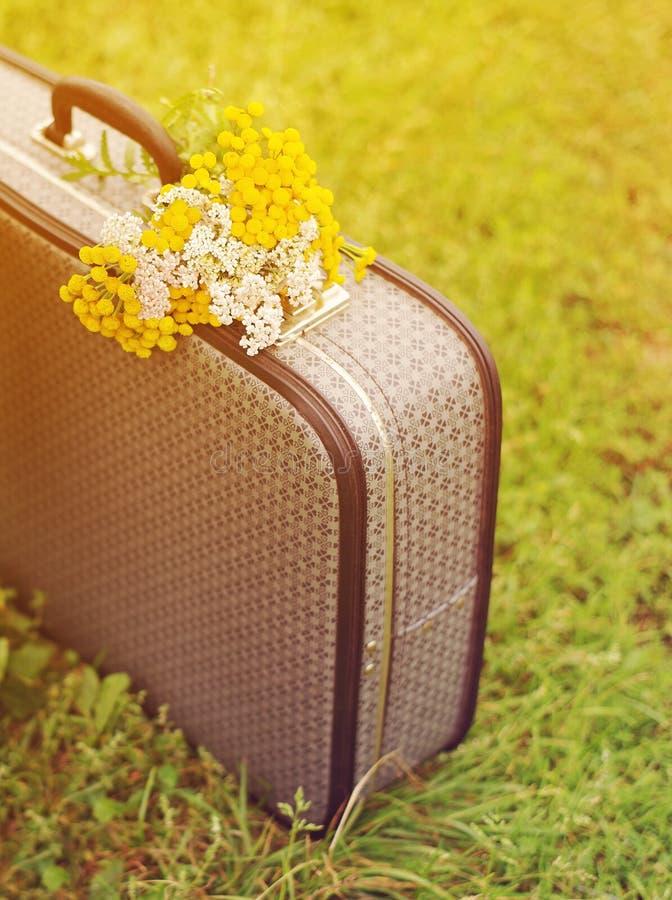 Mala de viagem e ramalhete cinzentos velhos de flores selvagens amarelas em uma grama verde no dia ensolarado do verão imagens de stock royalty free