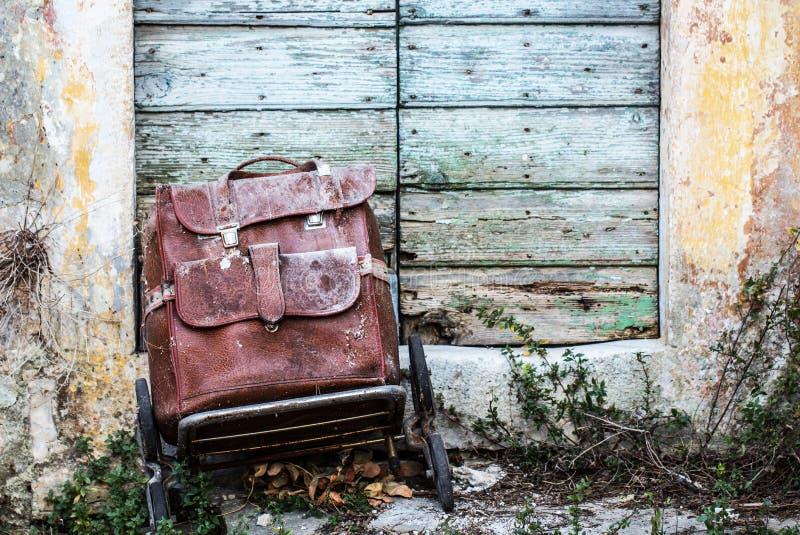 Mala de viagem marrom de couro retro do vintage velho no abandonedon o das rodas fotos de stock royalty free